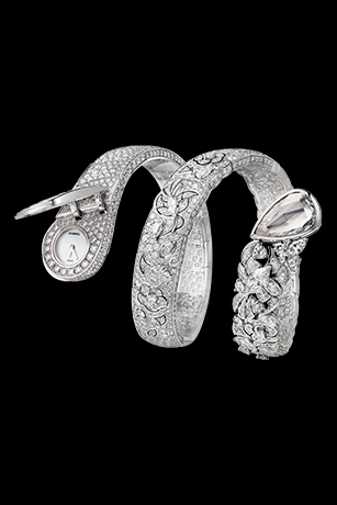 """The """"Ruban"""" watch is evolving ever so freely with a new version that wraps around the wrist. This delicate lace design watch in 18K gold set with 1,369 diamonds (including seven Fancy-cut diamonds) conceals a hidden watch dial on one side, and a 5-carat pear-cut diamond on the other."""